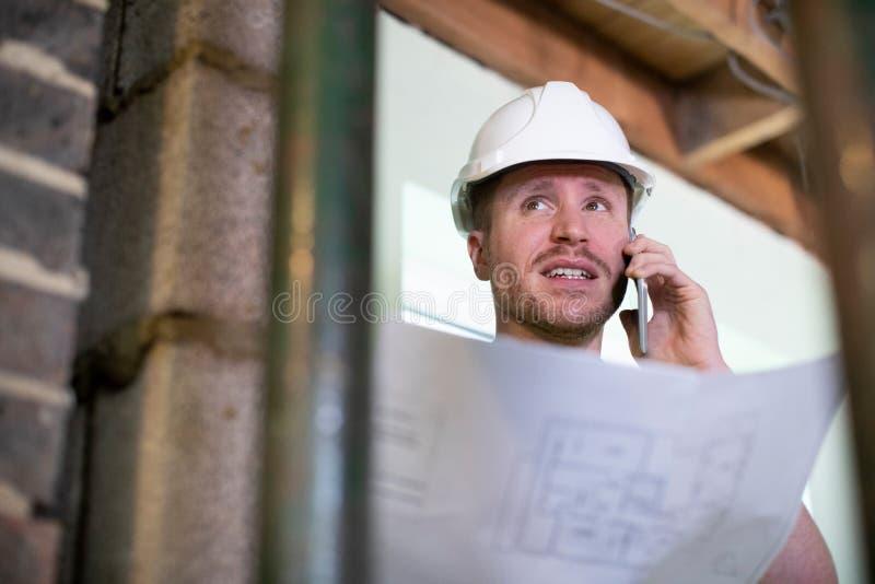 O arquiteto Inside House Being renovou o estudo de planos que fala no telefone celular imagem de stock royalty free