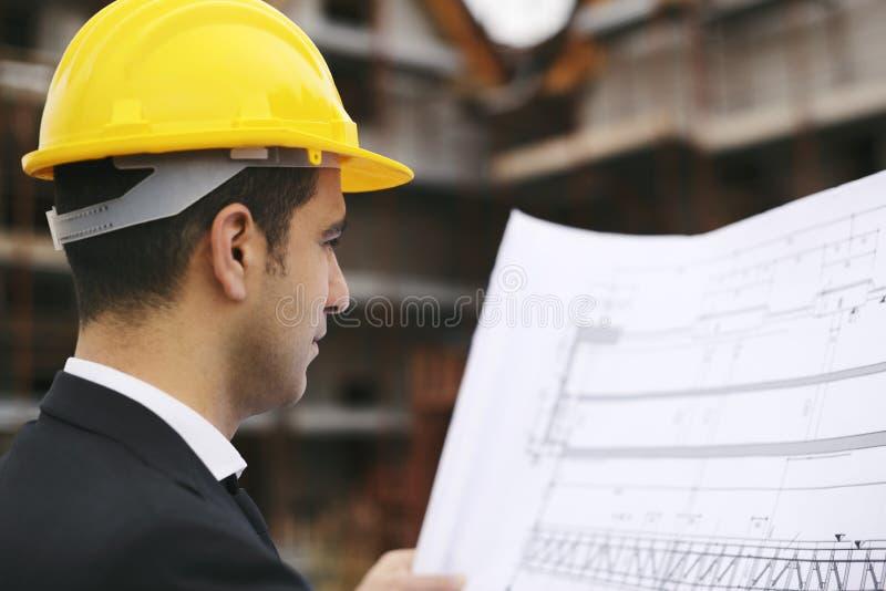 O arquiteto no canteiro de obras que olha a construção planeia fotografia de stock royalty free