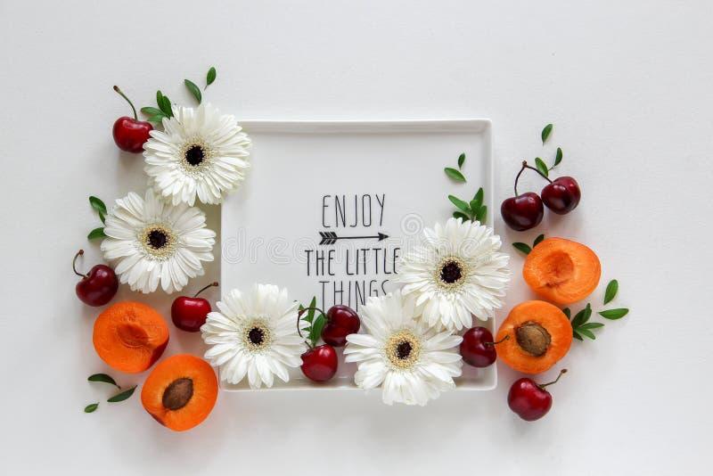 O arranjo das flores e os frutos em uma placa com nota 'apreciam as coisas pequenas ' fotos de stock