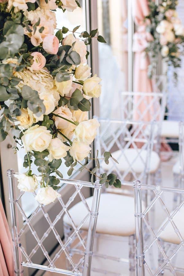 O arranjo de flor das rosas brancas e do eucalipto ao lado das cadeiras transparentes decora a zona da cerimônia de casamento no  imagem de stock