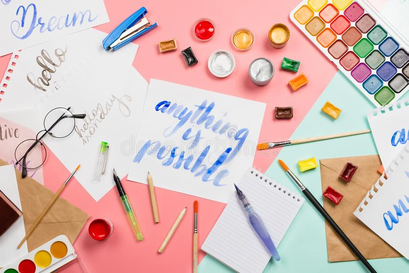 O arranjo flatlay bonito com aquarelas, escovas, vidros, brushpen, as pinturas com sinal handlettered qualquer coisa são possívei imagens de stock