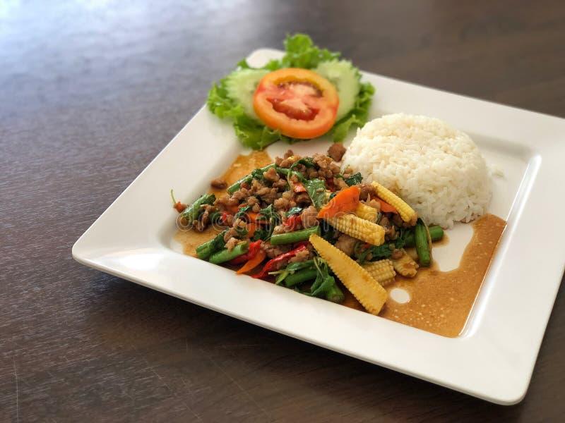 O arroz cobriu com carne de porco salteado e manjericão e vegetal, tomate no prato branco na tabela preta imagens de stock