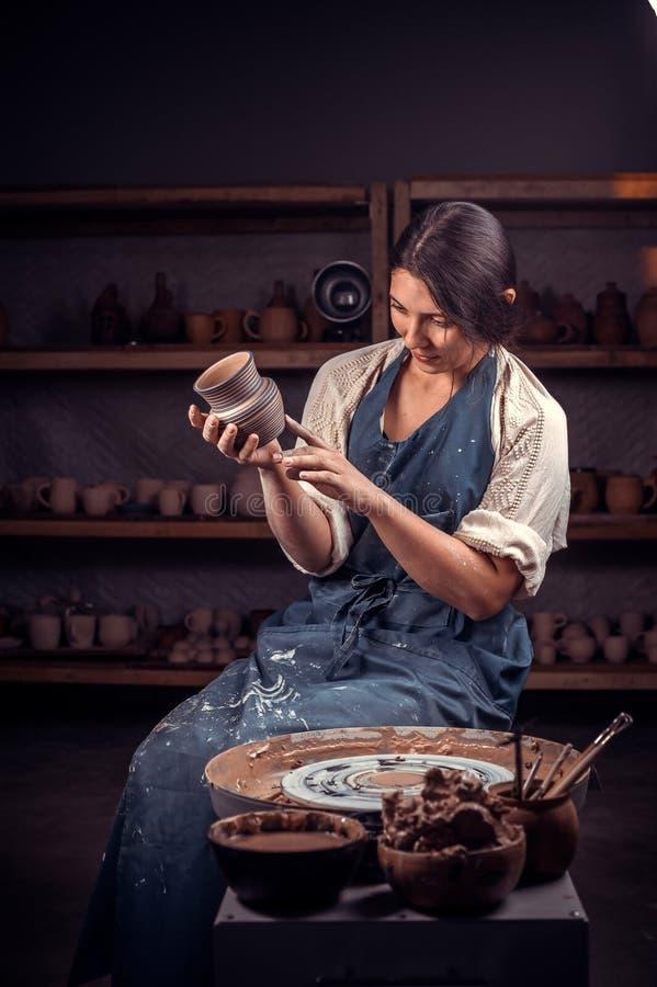 O artesão bonito demonstra o processo de fazer pratos cerâmicos usando a tecnologia velha ind?stria do artesanato foto de stock