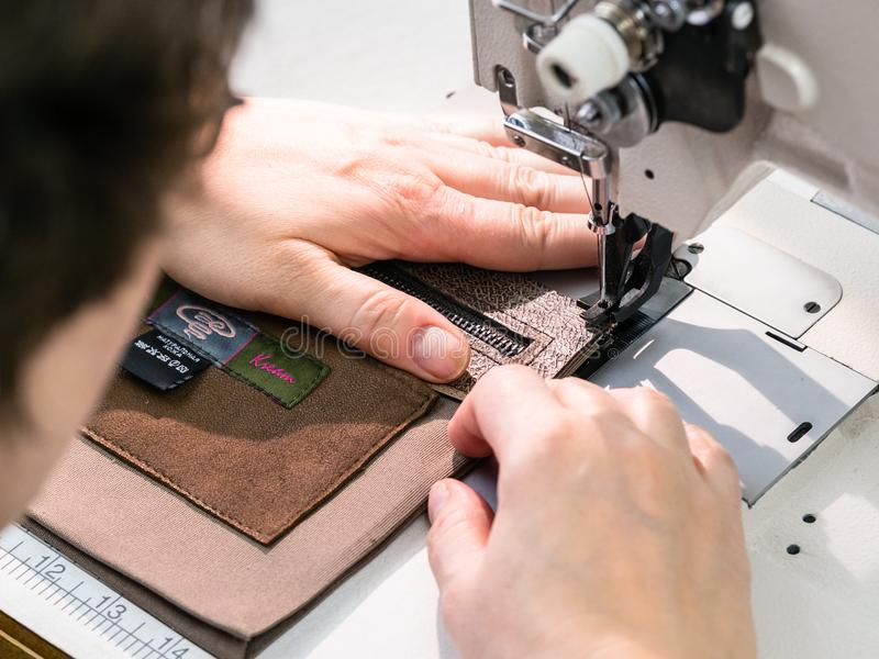 O artesão costura o bolso interno na máquina de costura imagens de stock royalty free
