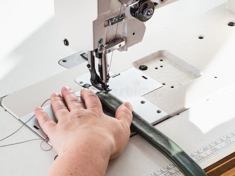 O artesão costura a correia para o saco na máquina de costura imagem de stock