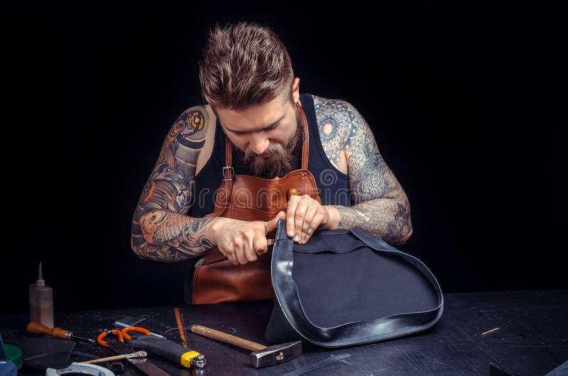 O artes?o de couro trabalha como um artes?o na loja do curtidor imagem de stock