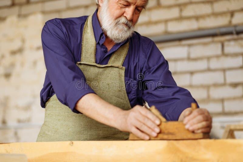 O artesão farpado com cabelo cinzento é bom no trabalho com pranchas imagens de stock royalty free
