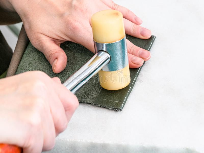 O artesão processa a borda do bolso pelo martelo foto de stock royalty free