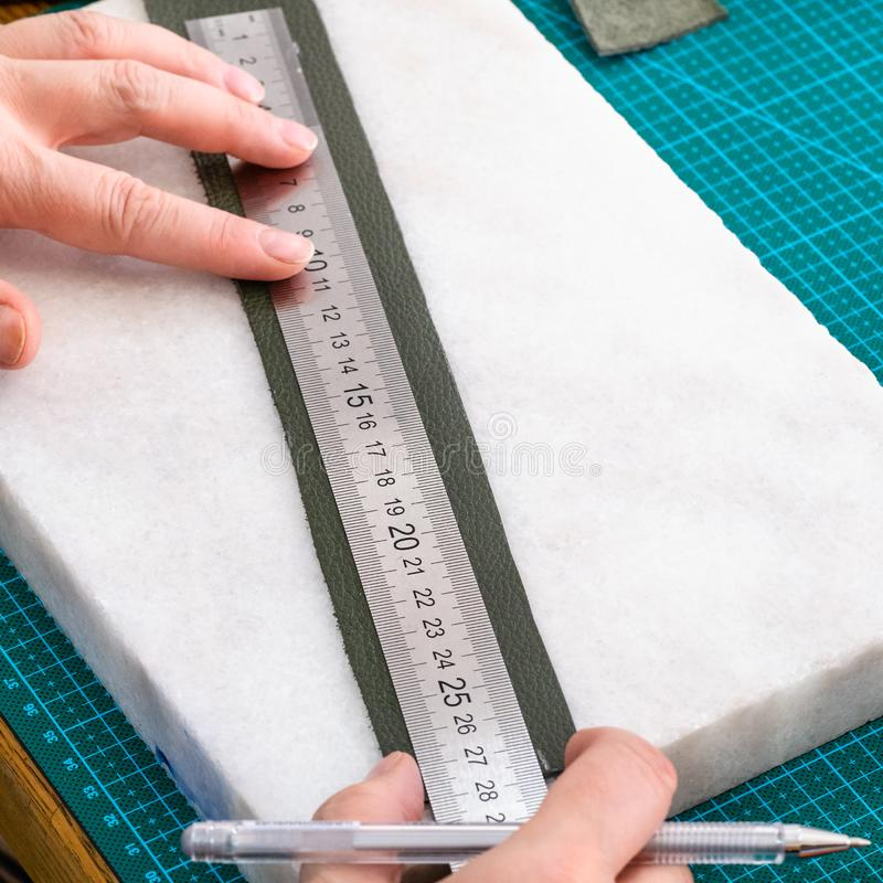 O artesão tira o teste padrão na placa da correia para o saco fotografia de stock royalty free