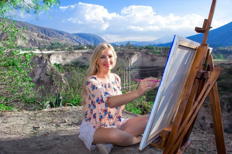 O artista bonito da jovem mulher pinta uma paisagem na natureza Tiragem na armação com pinturas coloridas no ar livre imagem de stock royalty free