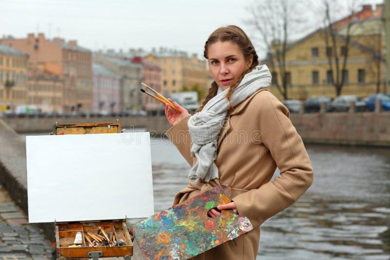 O artista com um bloco de desenho e uma lona na costa do ci fotos de stock royalty free