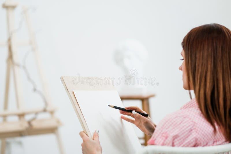 O artista da jovem mulher tira um lápis na lona fotos de stock royalty free