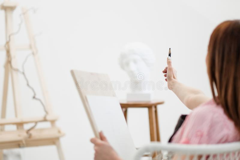 O artista da jovem mulher tira um lápis na lona fotografia de stock royalty free