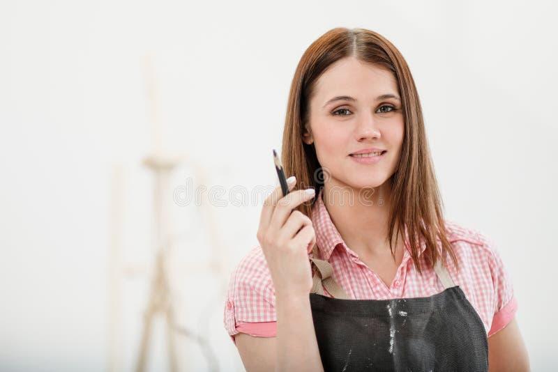 O artista da jovem mulher tira um lápis na lona imagens de stock