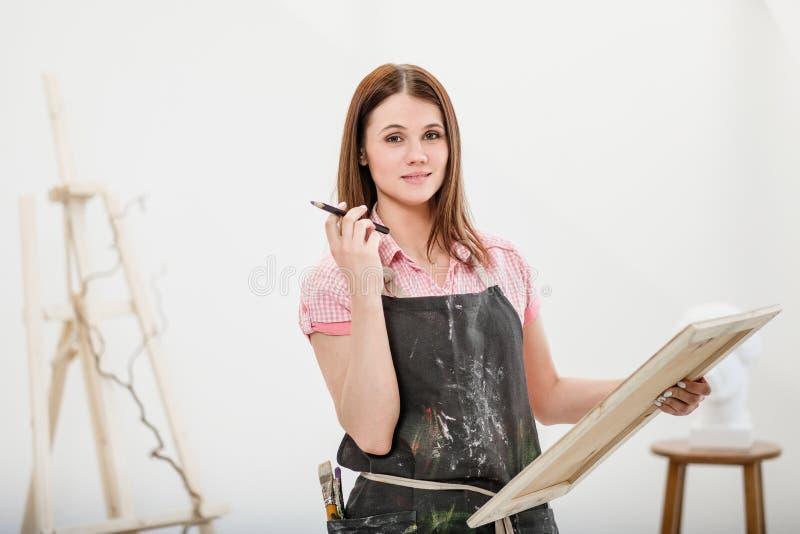 O artista da jovem mulher tira um lápis na lona fotos de stock