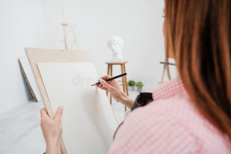 O artista da jovem mulher tira um lápis na lona fotografia de stock
