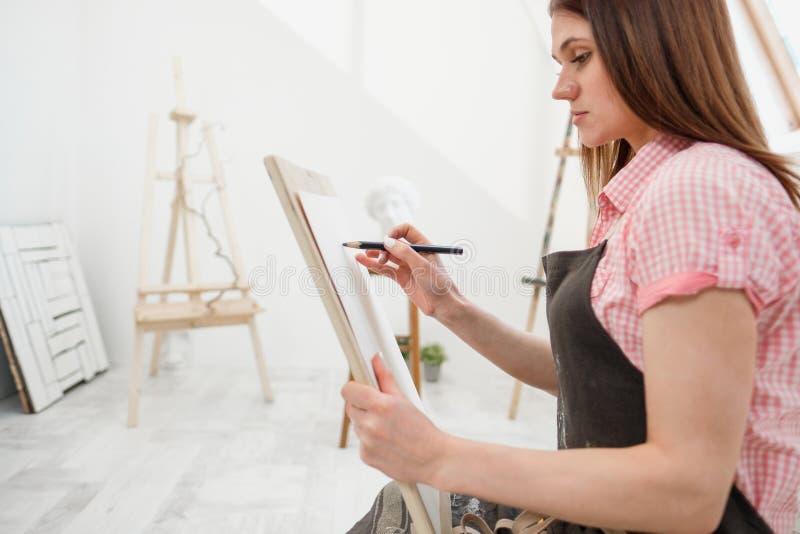 O artista da jovem mulher tira um lápis na lona imagem de stock