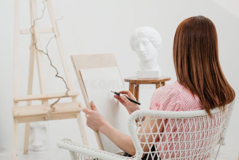 O artista da jovem mulher tira um lápis na lona foto de stock