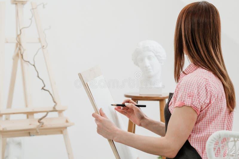 O artista da jovem mulher tira um lápis na lona foto de stock royalty free