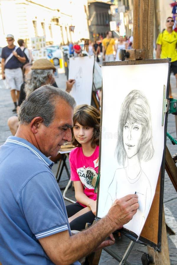 O artista da rua está fazendo um esboço do retrato de um turista novo imagem de stock