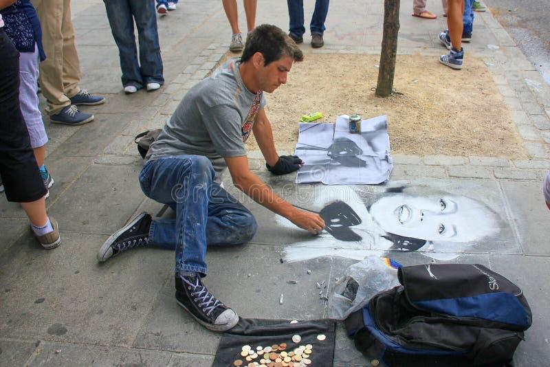 O artista da rua pinta o retrato da mulher no pavimento imagens de stock