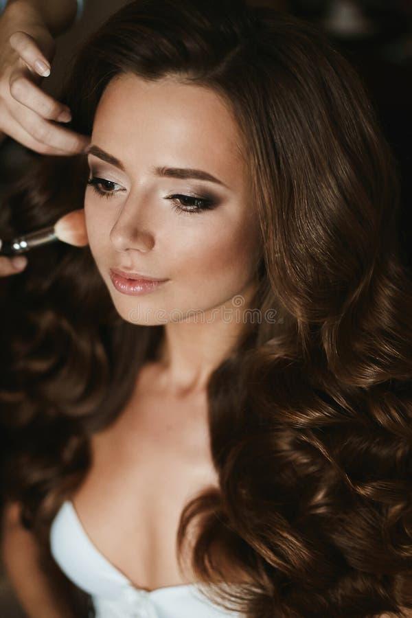O artista de composição aplica a composição do casamento para uma menina modelo moreno bonita com penteado à moda e em uma roupa  foto de stock royalty free