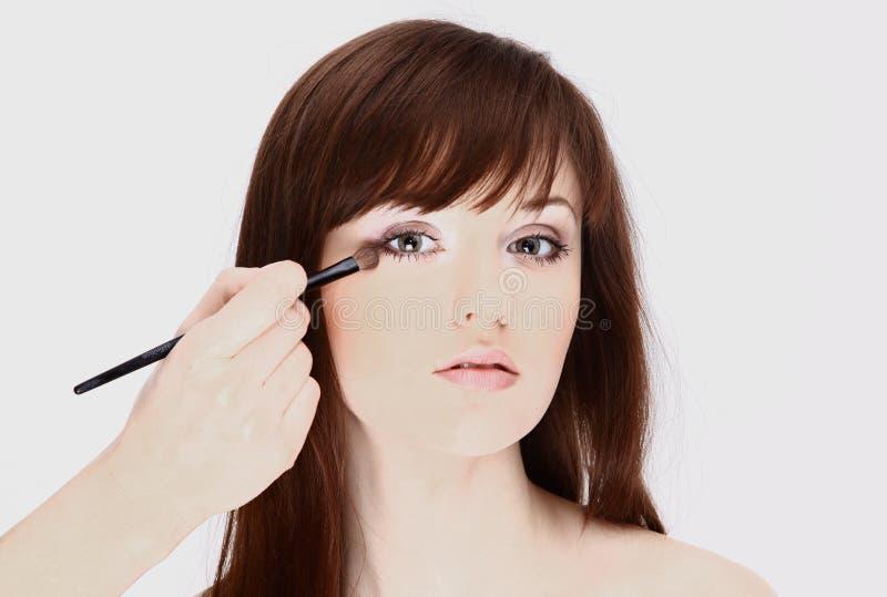 O artista de composição aplica a sombra de olho Face bonita da mulher imagem de stock royalty free