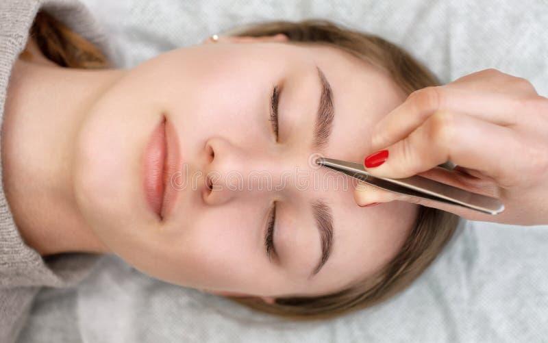 O artista de composição arranca suas sobrancelhas de uma jovem mulher em um salão de beleza imagens de stock
