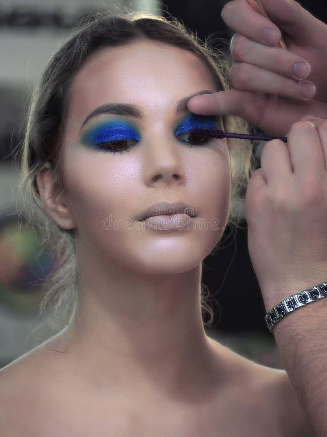 O artista de composição faz a pintura da composição da arte nas pestanas de pintura do olho dos modelos imagens de stock