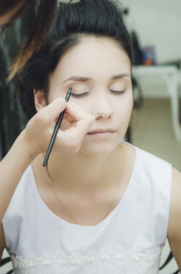 O artista de composição pinta as sobrancelhas à morena da menina, close-up imagens de stock royalty free