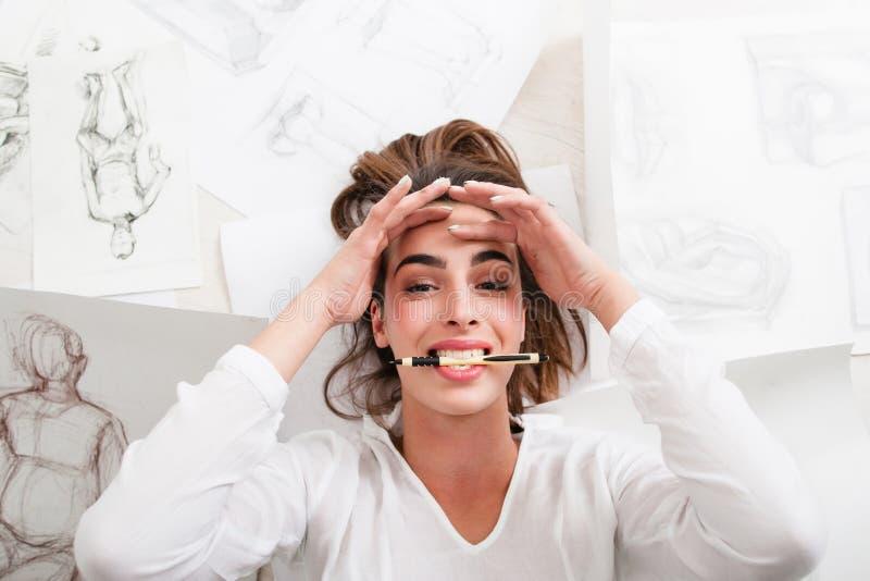 O artista de sorriso que encontra-se no assoalho mordeu a opinião superior do lápis imagem de stock