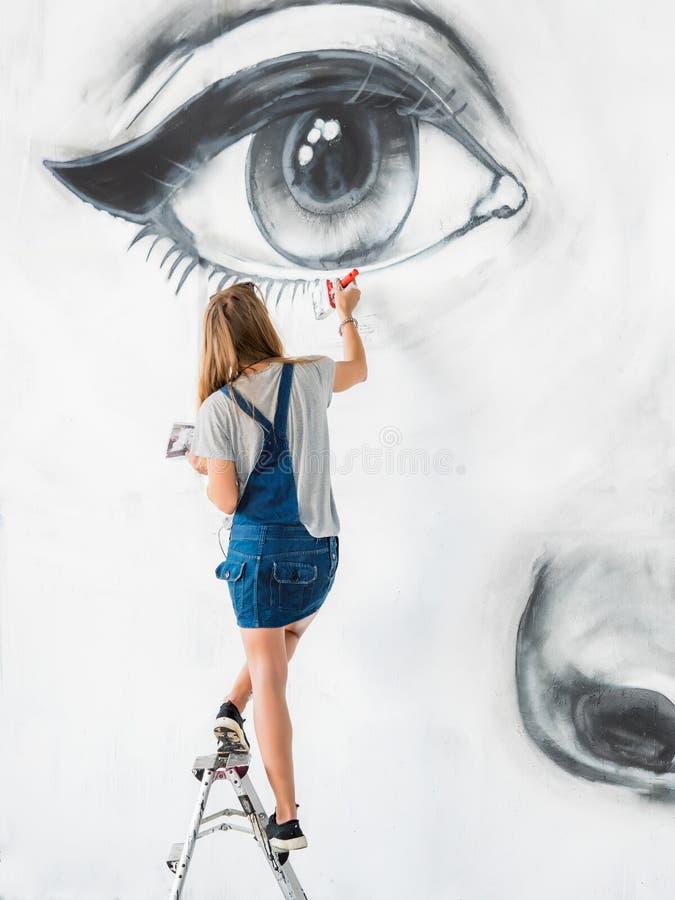 O artista Drawing dos grafittis enfrenta da mulher bonita com pintura na parede da rua Trabalho fêmea com escova Arte urbana do a imagem de stock