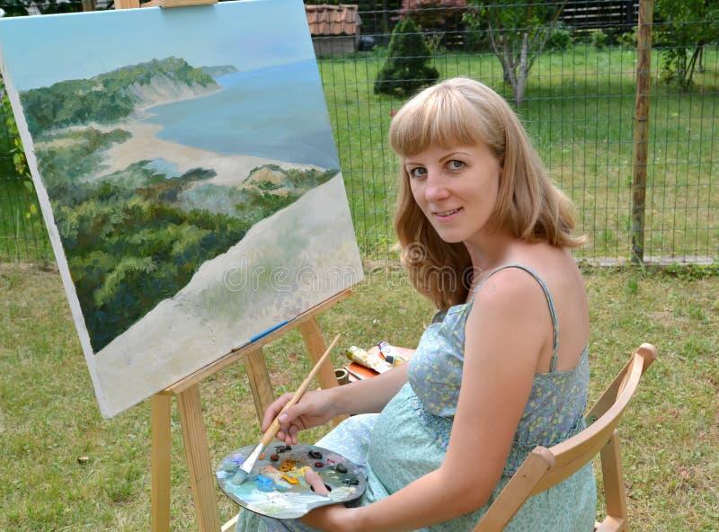 O artista fêmea grávido novo pinta uma imagem, sentando-se em uma armação imagens de stock