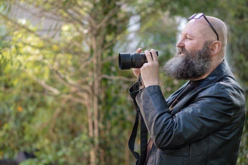 O artista louco idiossincrásico com barba, guarda uma câmera de sistema digital imagens de stock