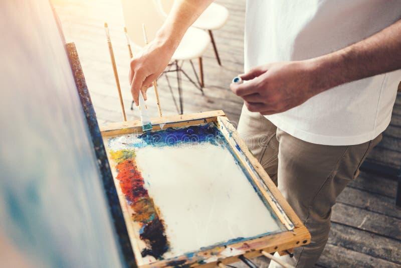 O artista masculino mistura cores na paleta no estúdio Pintor na oficina fotos de stock