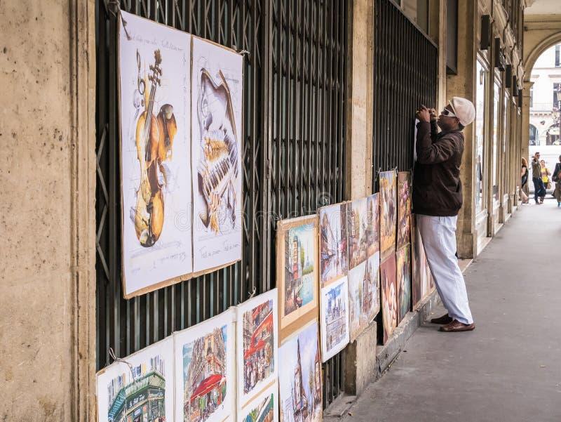 O artista pendura suas pinturas em uma grelha do ferro, Paris, França fotografia de stock