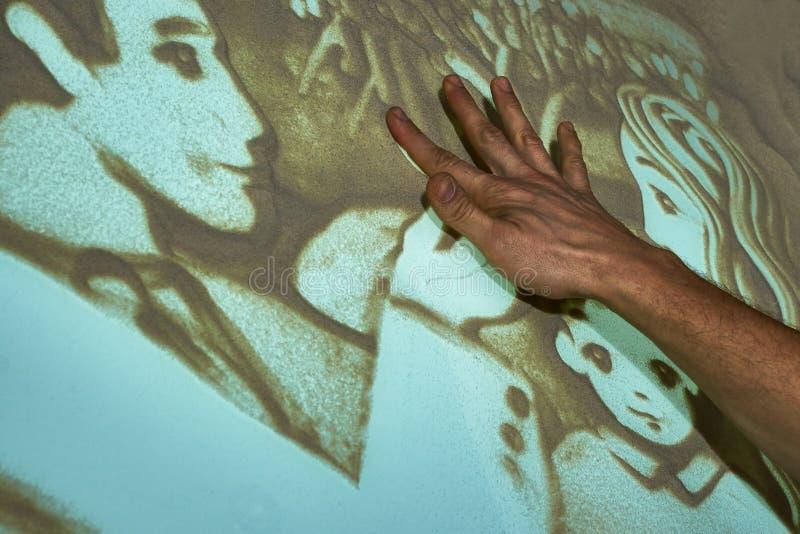 O artista pinta a areia fotografia de stock