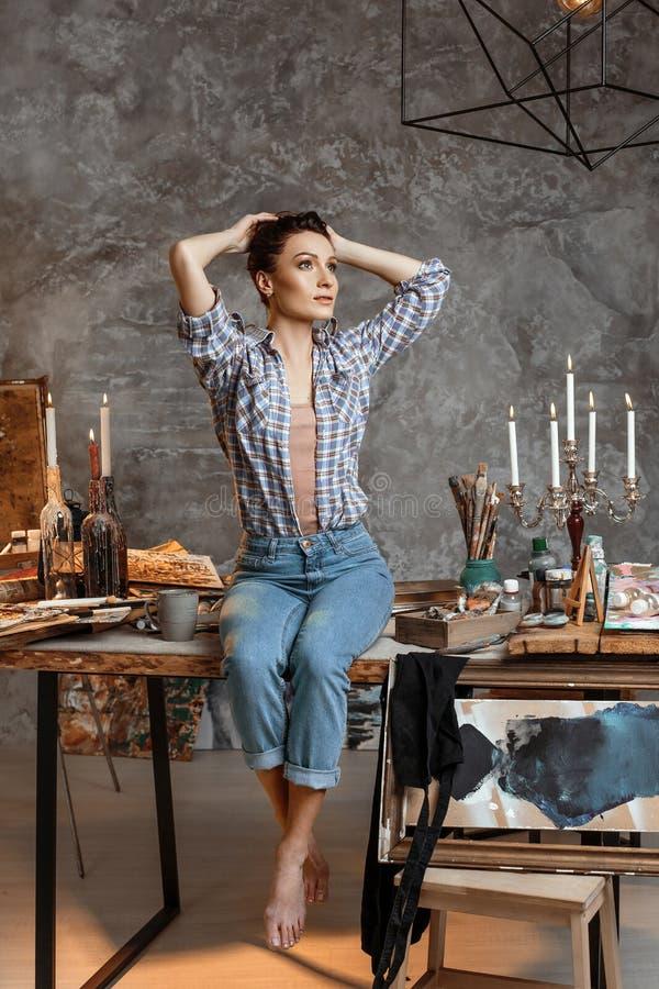 O artista talentoso novo bonito que senta-se em uma tabela na oficina é preparado para a criação de uma obra-prima nova foto de stock royalty free