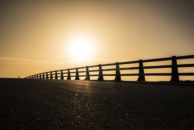 O asfalto da estrada no ciclismo do por do sol ostenta a motivação fotografia de stock royalty free