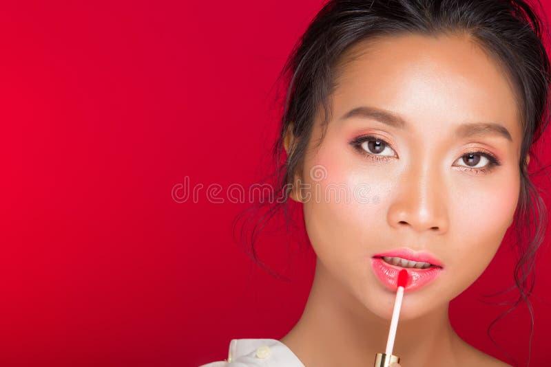 O asiático bronzeou-se a mulher da pele com os bordos fortes do vermelho da cor fotografia de stock royalty free