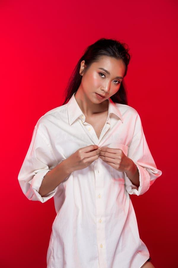 O asiático bronzeou-se a mulher da pele com os bordos fortes do vermelho da cor foto de stock royalty free
