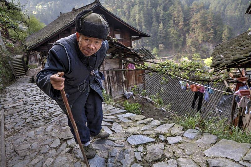 O asiático envelhecido anda ao longo da estrada de pedra, colocando em sua vara fotografia de stock royalty free