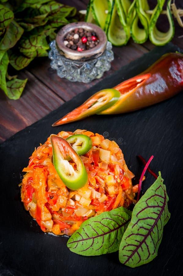 o Asiático-estilo frita mexendo o cozimento do vegetal quente faz saltar na ardósia, fundo de madeira, beringelas, pimenta de pim imagens de stock royalty free