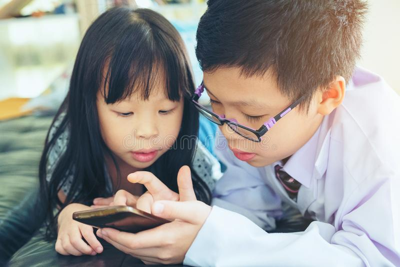 O asiático Tailândia duas crianças menino e menina senta-se junto na cama dentro fotografia de stock