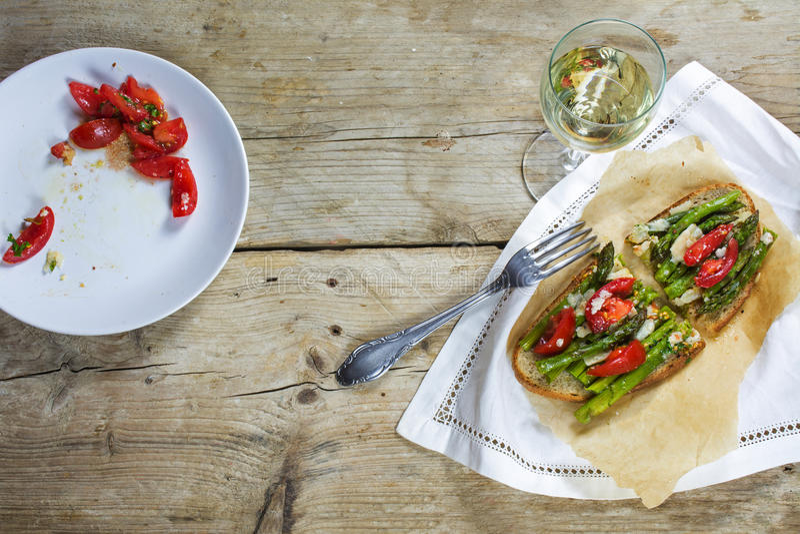 O aspargo, os tomates e o Parmesão verdes gratinated no pão e no a imagens de stock