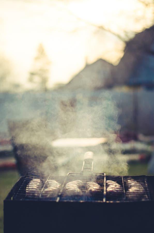 O assado a preparar-se no quintal/salsichas de um assado prepara-se no ar livre foto de stock