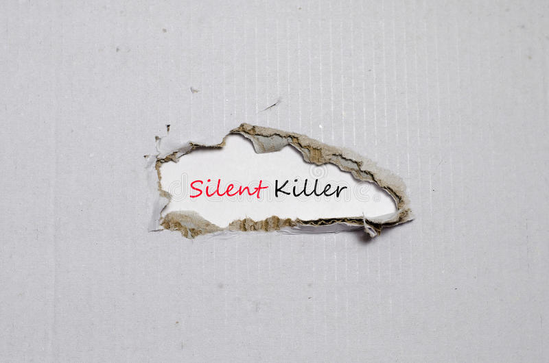 O assassino silencioso da palavra que aparece atrás do papel rasgado foto de stock royalty free