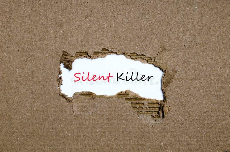 O assassino silencioso da palavra que aparece atrás do papel rasgado imagem de stock royalty free