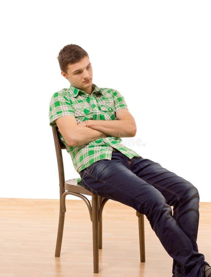 O assento considerável do homem novo caiu em uma cadeira imagem de stock