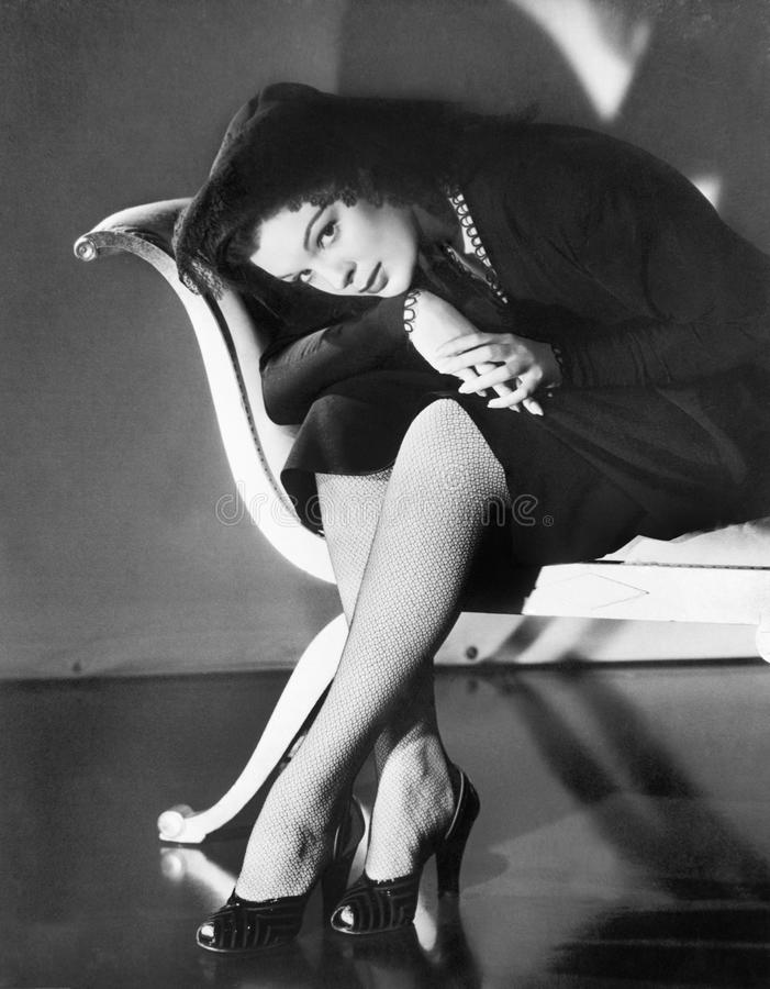 O assento da jovem mulher cruzou equipado com pernas, dobrando-se sobre (todas as pessoas descritas não são umas vivas mais longo imagens de stock